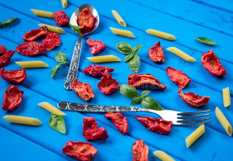 Fondo delle fette seccate al sole del pomodoro con le foglie del basilico e la pasta del penne sulla tavola di legno blu fotografia stock