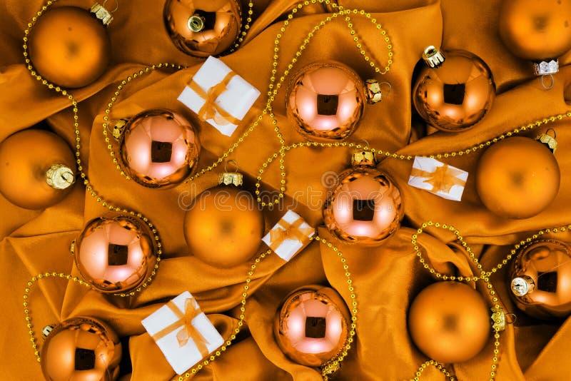 Fondo delle palle arancio dell'albero di Natale, pochi contenitori di regalo e decorazioni dell'oro su tessuto di seta arancio fotografie stock libere da diritti