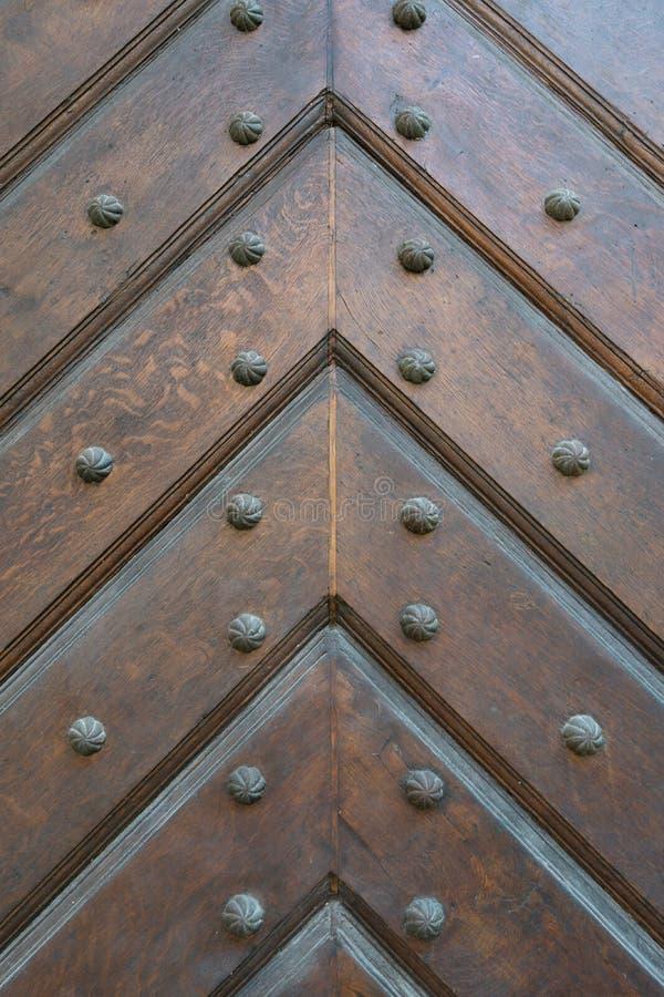 Fondo delle plance di legno piegate in direzione della freccia su, cucito con i bulloni neri del metallo con una testa scolpita fotografia stock
