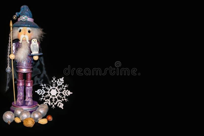 Fondo delle schiaccianoci dello stregone - figura porpora con il fiocco di neve ed i dadi e le palle di Natale, tenendo un person fotografia stock libera da diritti