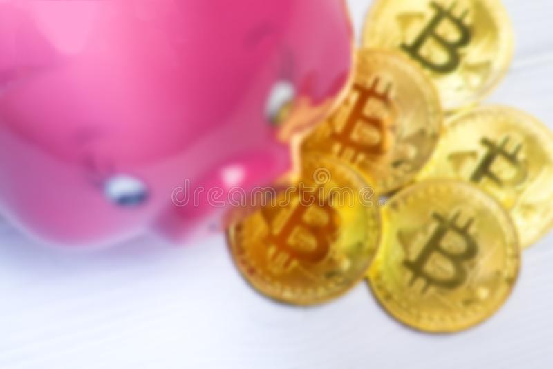 Fondo di Blury dei bitcoins della banca del maiale e di un oro di goccia sui precedenti di legno bianchi immagini stock