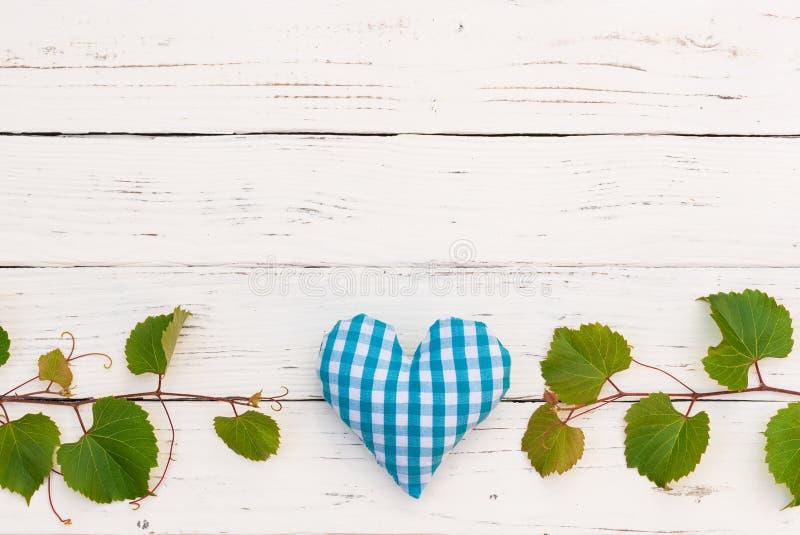 Fondo di celebrazione di evento dell'assaggio di vino con il confine della vigna ed il cuore blu sulla tavola di legno bianca immagini stock libere da diritti