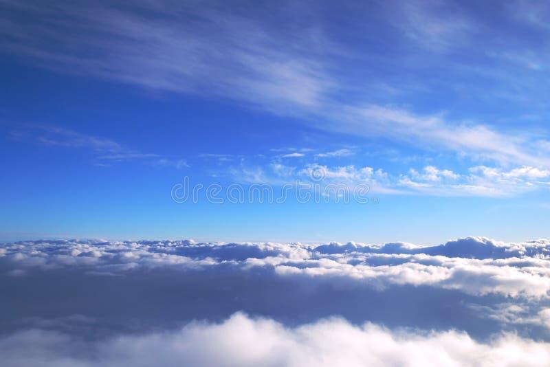 Fondo di cielo blu sopra i cumuli con i raggi del tramonto fotografia stock