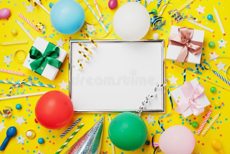 Fondo di compleanno o del partito Struttura d'argento con il pallone, il regalo, il cappuccio di carnevale, i coriandoli, la cara immagine stock libera da diritti