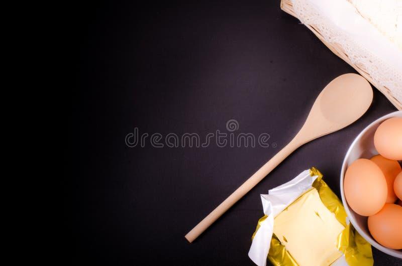 Fondo di cottura con le orecchie di grano, di farina, delle uova e del burro fotografia stock