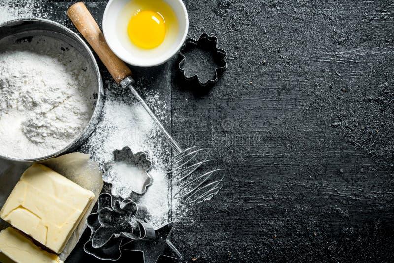 Fondo di cottura Farina con l'uovo, il burro e le varie forme per cuocere fotografia stock