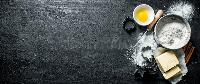Fondo di cottura Farina con l'uovo, il burro e le varie forme per cuocere immagine stock