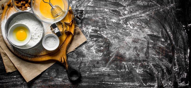 Fondo di cottura Farina in un setaccio con i dadi e le forme per pasta fotografia stock