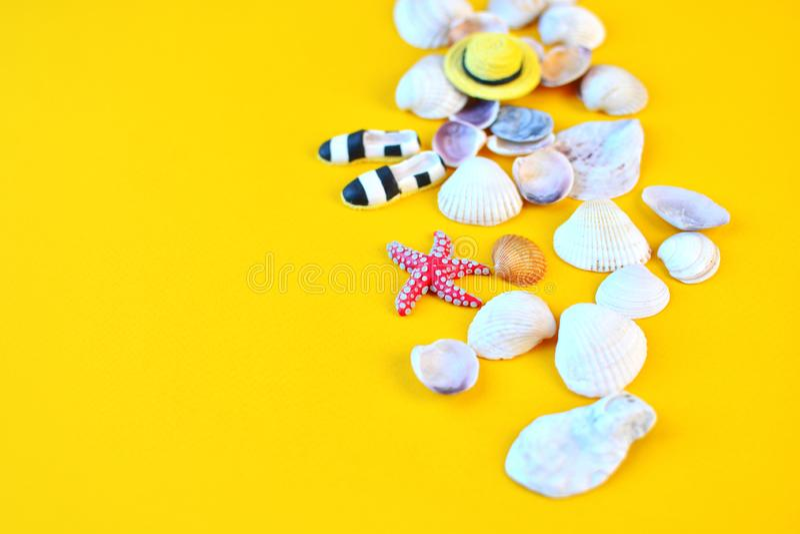 Fondo di estate Accessori posti piani della spiaggia del viaggiatore su fondo giallo con le conchiglie, il cappello miniatura ed  immagine stock libera da diritti