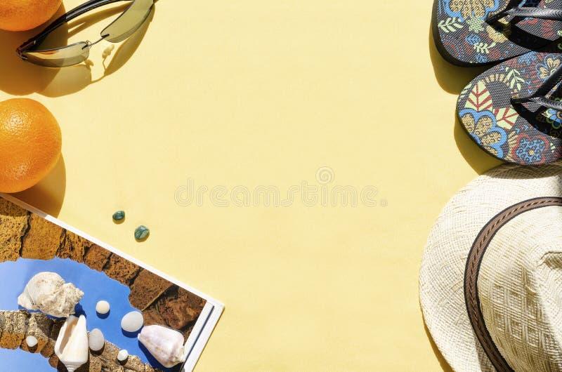Fondo di estate Disposizione piana del cappello di paglia, degli occhiali da sole, dei Flip-flop e delle conchiglie su fondo gial immagine stock libera da diritti