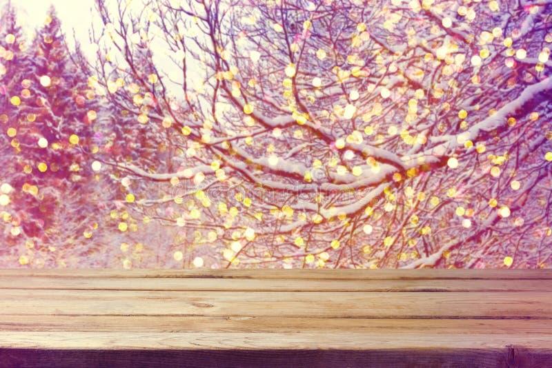Fondo di festa di Natale con il bokeh di legno delle luci e della tavola sugli alberi immagine stock