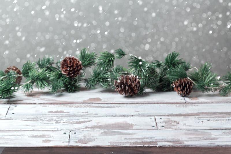 Fondo di festa di Natale con la tavola bianca di legno vuota e le luci festive di Natale fotografia stock