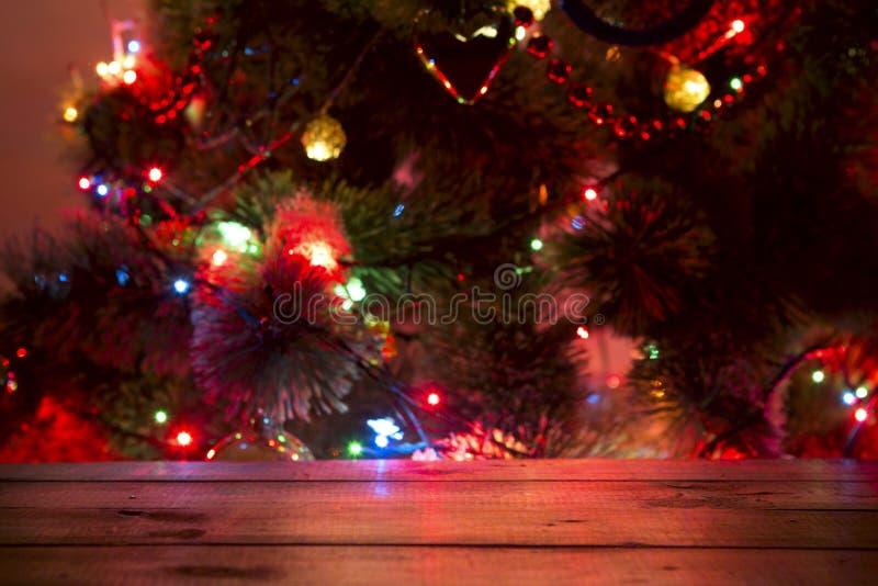 Fondo di festa di Natale con la tavola di legno vuota della piattaforma sopra bokeh fotografia stock libera da diritti