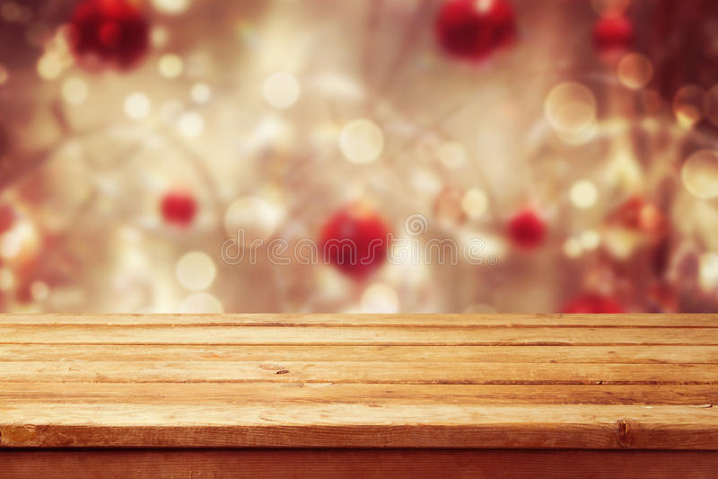 Fondo di festa di Natale con la tavola di legno vuota della piattaforma sopra il bokeh di inverno Aspetti per il montaggio del pr immagine stock