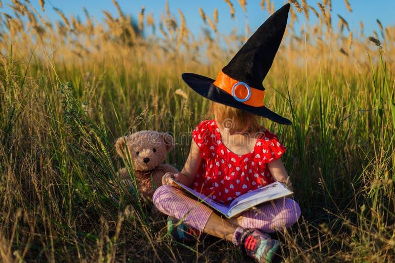 Fondo di festa di Halloween: bambina in un cappello della strega che si siede sull'erba con un orsacchiotto e che legge un libro fotografia stock