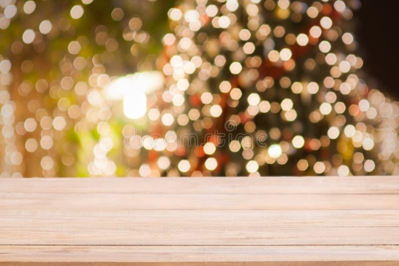 Fondo di festa di Natale con il piano d'appoggio di legno vuoto sopra la luce festiva del bokeh immagine stock