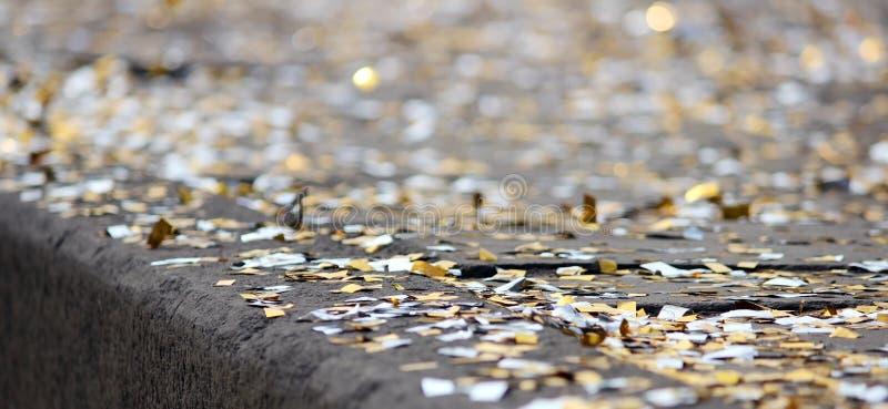 fondo di festival con gli zecchini dell'argento e dell'oro che si trovano sulla pavimentazione il bokeh della strada fotografia stock libera da diritti