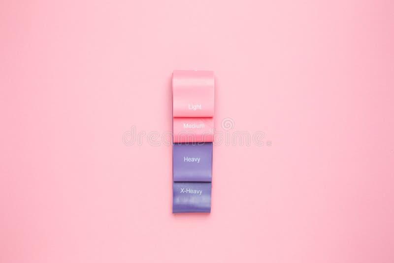 Fondo di forma fisica Bande elastiche per l'allungamento su uno spazio rosa pastello della copia del fondo immagini stock