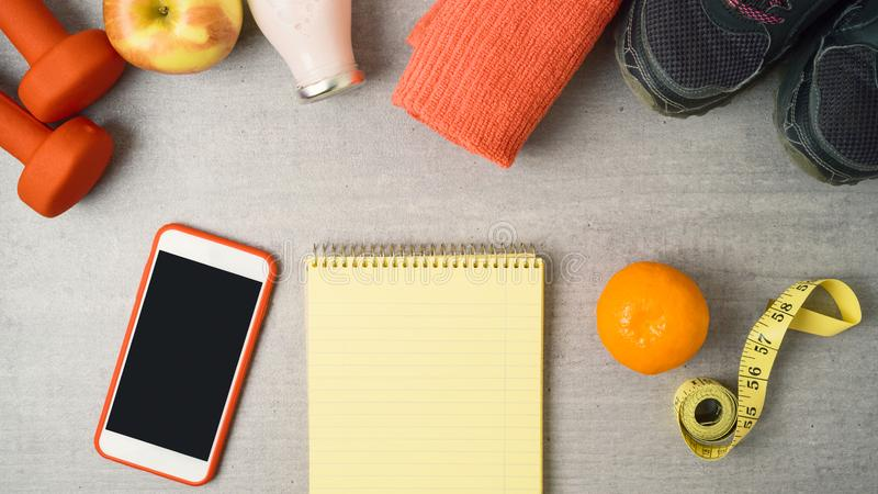 Fondo di forma fisica con il blocco note, le teste di legno, la scossa della proteina, lo smartphone e l'asciugamano immagine stock libera da diritti