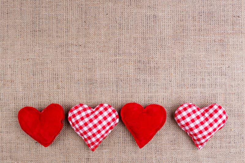 Fondo di giorno di biglietti di S. Valentino con i cuori del tessuto su tela di sacco, copia fotografia stock