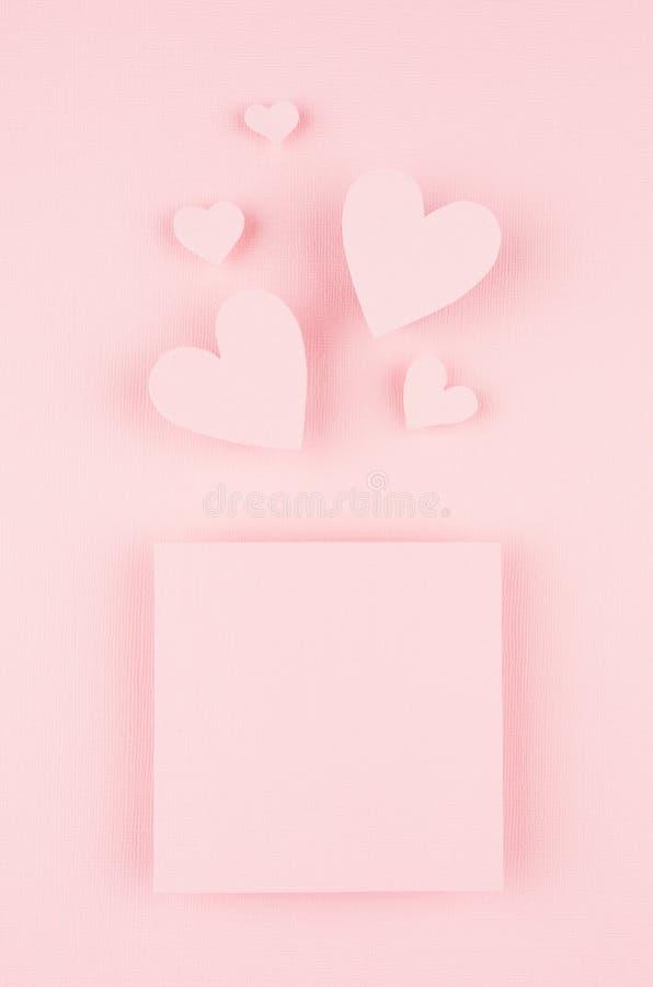 Fondo di giorno di biglietti di S. Valentino con i cuori della carta e della pagina in bianco sul fondo rosa delicato di colore fotografia stock