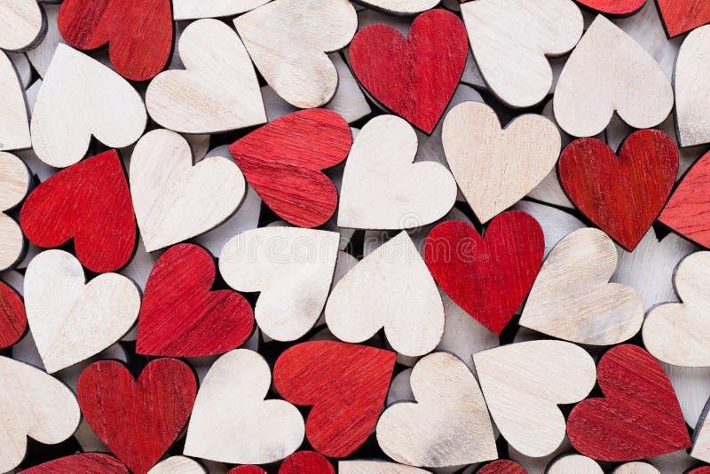 Fondo di giorno di biglietti di S. Valentino con i cuori rossi dell'estremità bianca su fondo di legno immagini stock