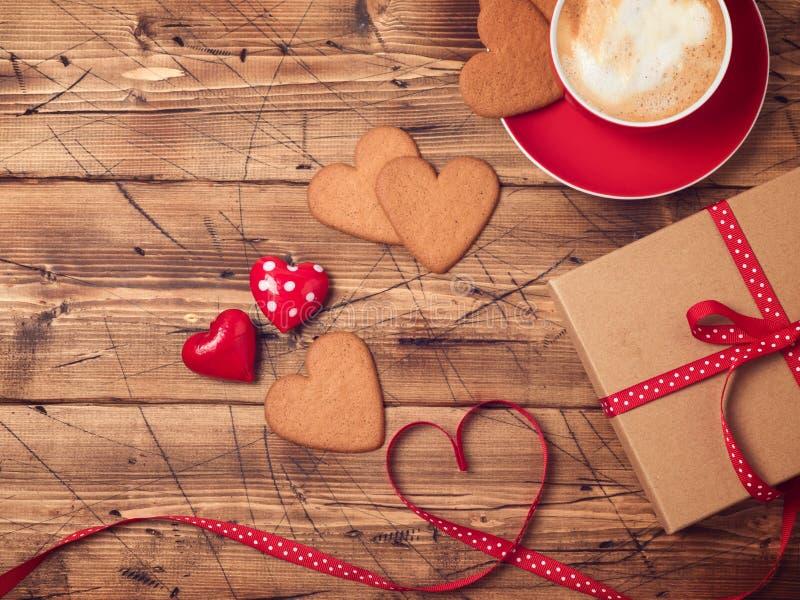 Fondo di giorno di biglietti di S. Valentino con la tazza di caffè, i biscotti di forma del cuore ed il contenitore di regalo fotografie stock