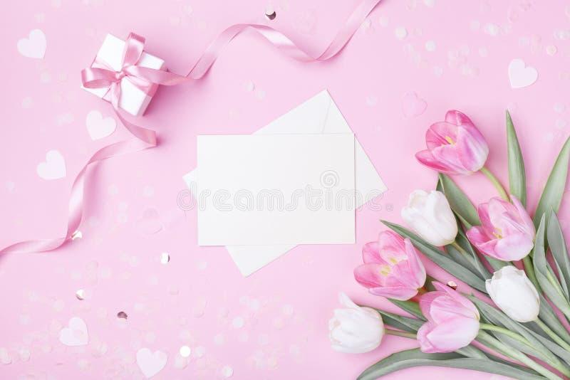 Fondo di giorno delle donne giorno, di madre con la busta, contenitore di regalo e bei fiori del tulipano della molla sullo scrit immagine stock libera da diritti