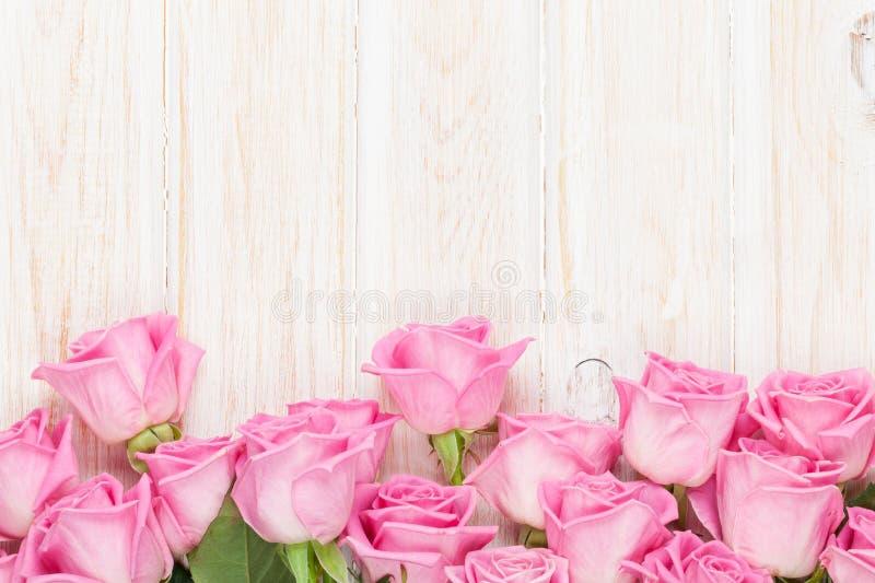 Fondo di giorno di biglietti di S. Valentino con le rose rosa sopra la tavola di legno fotografia stock