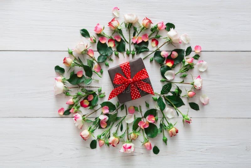 Fondo di giorno di S. Valentino, contenitore di regalo e fiori su legno bianco fotografia stock