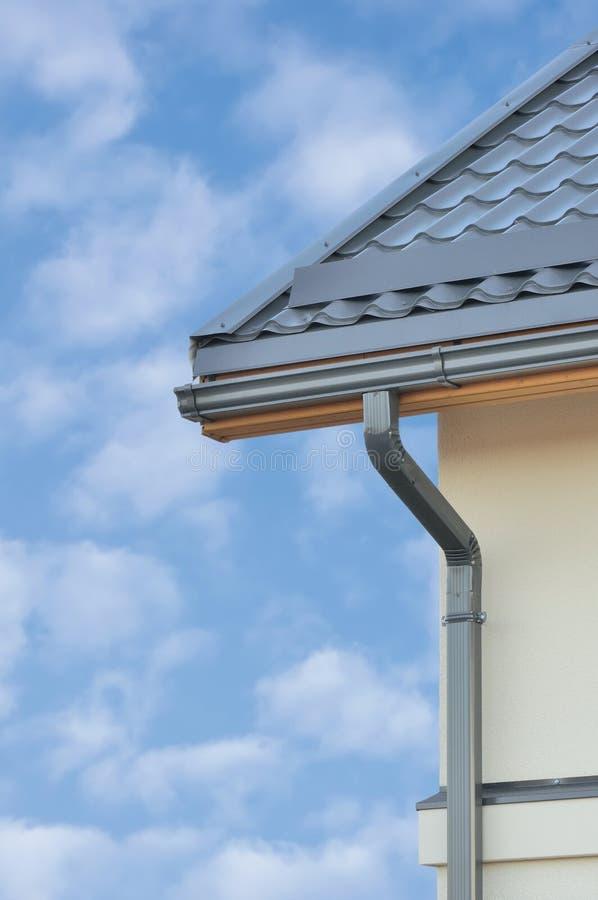 Fondo di Grey Steel Tile Roof Texture, Gray Tiled Roofing, parete intonacata giallo beige, grondaia della pioggia, grande vertica immagine stock libera da diritti