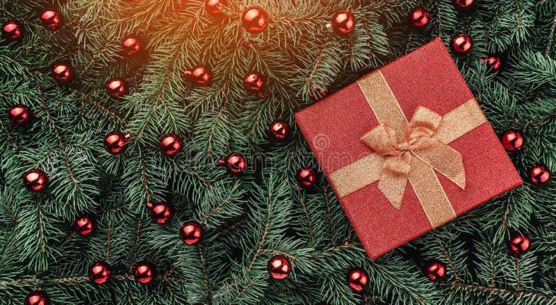 Fondo di inverno dei rami dell'abete Ornato con le bagattelle ed il regalo rossi Cartolina di Natale Vista superiore Congratulazi fotografia stock
