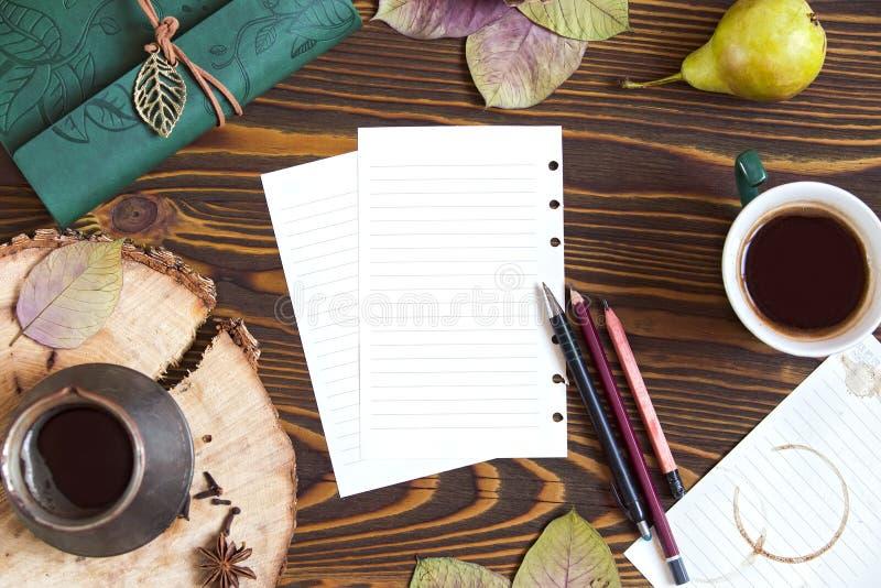 Fondo di legno con carta per le note, latteria, cofee, ezve del  di Ñ, foglie di autunno Vista superiore del posto di lavoro fotografia stock
