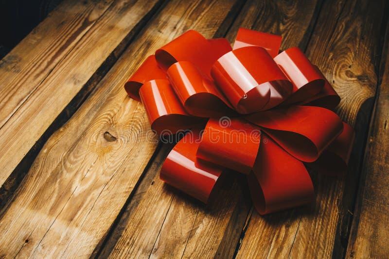 Fondo di legno con l'arco rosso e nastro con la fine dello spazio della copia su immagine stock libera da diritti