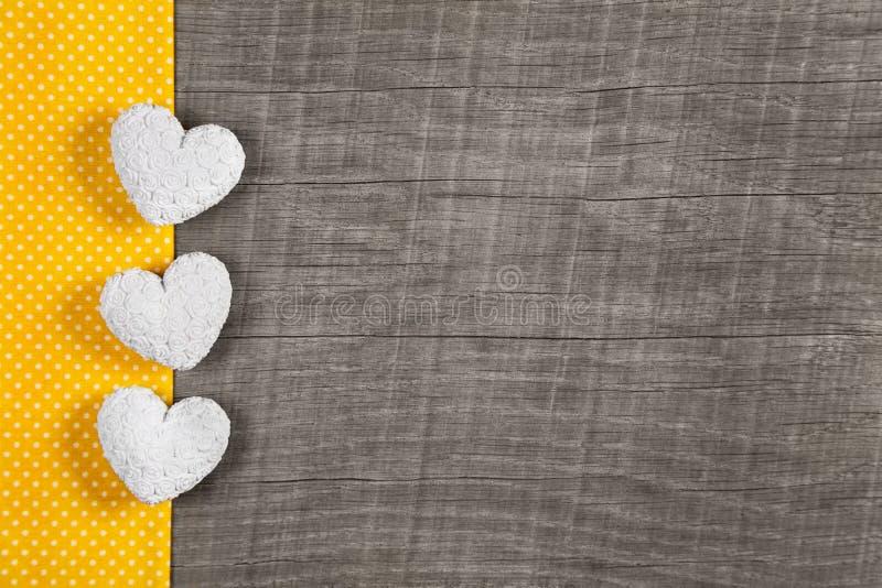Fondo di legno con tre bianchi e cuori gialli sulla b di legno fotografia stock