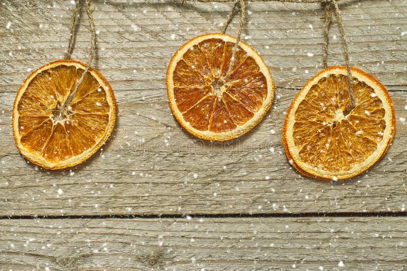 Fondo di legno d'annata con la corona di Natale - le fette arancio secche appendono sulla corda e sulla neve di caduta Cartolina  immagine stock