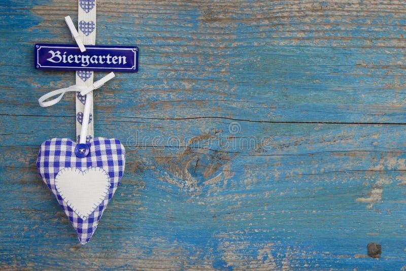 Fondo di legno del blu bavarese con cuore e testo fotografia stock