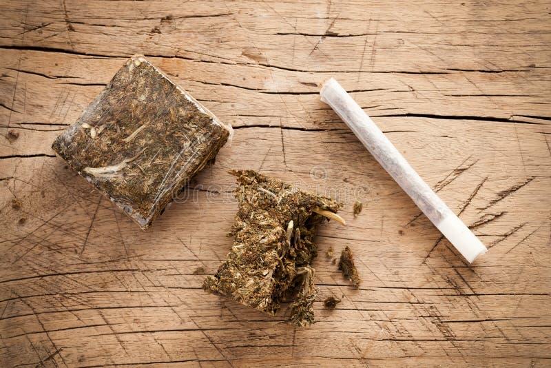 Fondo di legno del rotolo dell'hashish della marijuana dell'erbaccia immagini stock
