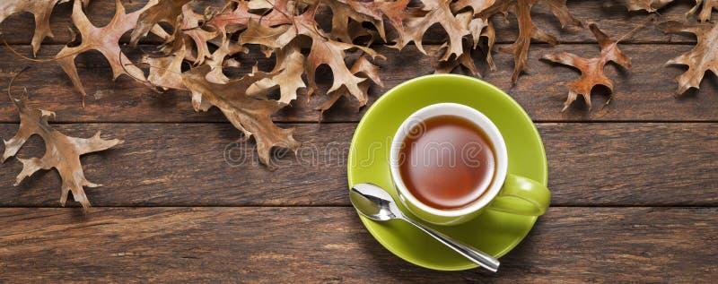 Fondo di legno della tazza di tè delle foglie immagine stock libera da diritti