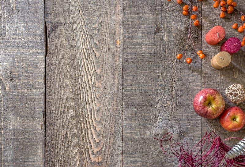 Fondo di legno rustico della plancia con le candele, le mele ed i ber di autunno immagine stock libera da diritti
