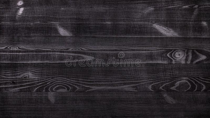 Fondo di legno rustico nero della tavola con una struttura distinta delle fibre di legno e nodi con il modello orizzontale per il fotografia stock