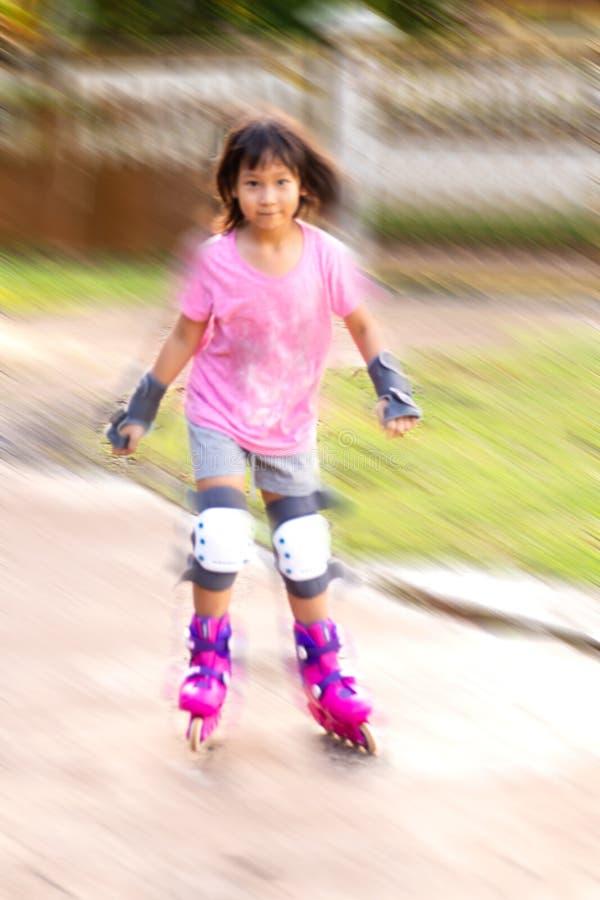 Fondo di moto della sfuocatura Ragazza asiatica che gioca rollerblading a casa immagini stock libere da diritti