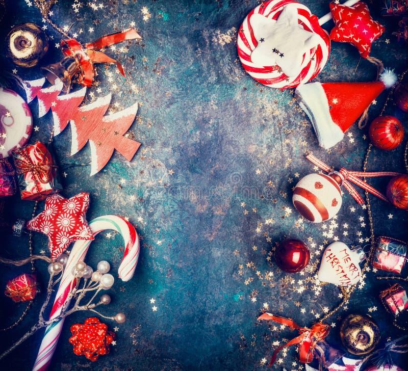 Fondo di Natale con i dolci e le decorazioni rosse di festa: Cappello di Santa, albero, stella, palle, vista superiore fotografia stock libera da diritti