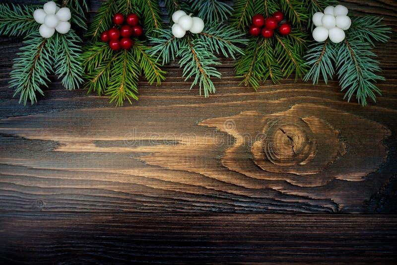 Fondo di Natale con i rami e le bacche dell'abete sul bordo di legno di lerciume Copi lo spazio fotografie stock libere da diritti