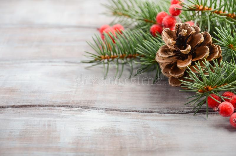 Fondo di Natale con i rami, le bacche ed i coni dell'abete fotografia stock libera da diritti