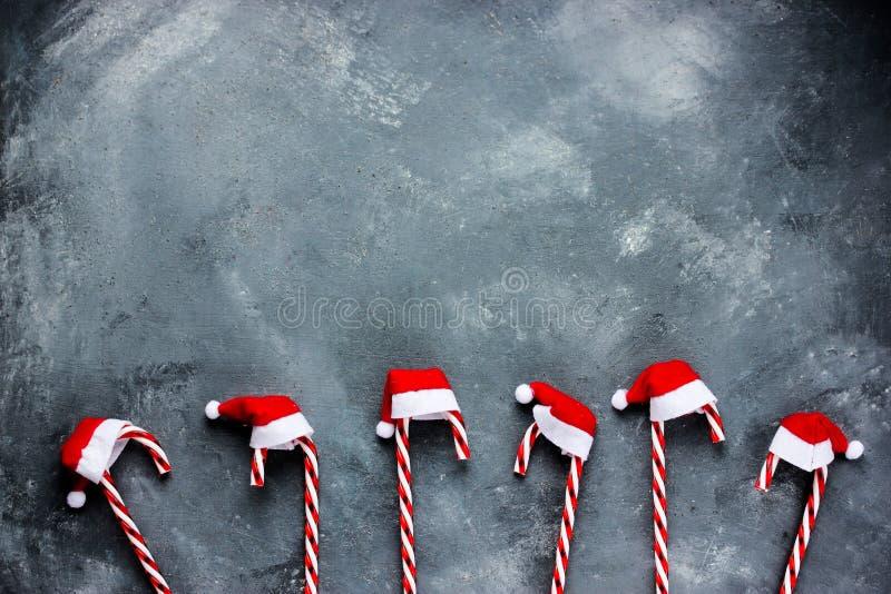 Fondo di Natale con il bastoncino di zucchero in cappello di Santa, spazio o immagini stock libere da diritti