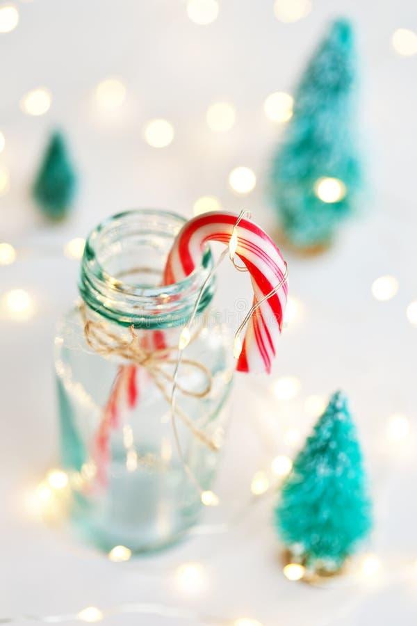 Fondo di Natale con il bastoncino di zucchero e la luce di Natale fotografia stock