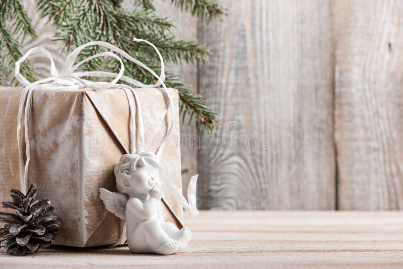 Fondo di Natale con il contenitore di regalo e poco angelo fotografie stock libere da diritti