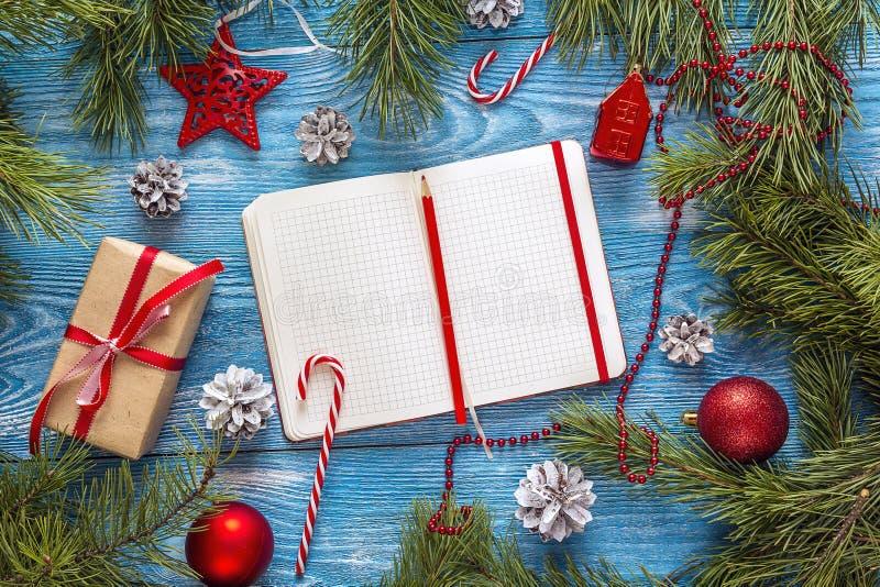 Fondo di Natale con il taccuino, i rami dell'abete, le decorazioni ed il contenitore di regalo in bianco Spazio per testo Lista d immagine stock libera da diritti