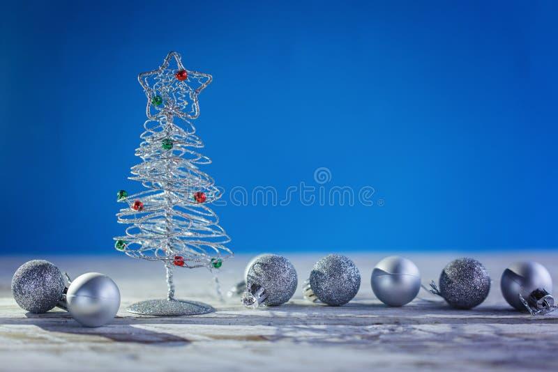 Fondo di Natale con l'albero di Natale d'argento decorativo e palla su fondo blu immagini stock libere da diritti